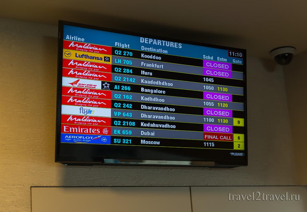 табло рейсов в бизнес-зале в Мале Moonimaa Priority Pass внутренние рейсы, Мальдивы